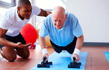 Trainer helping senior citizen do push-ups (iStockphoto)