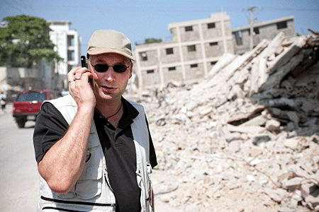 Man on phone in front of building destroyed by quake (iStockphoto)