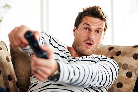 Young man playing video game (iStockphoto)