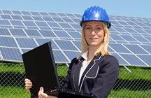 Environmental engineer with computer, in front of solar panels
